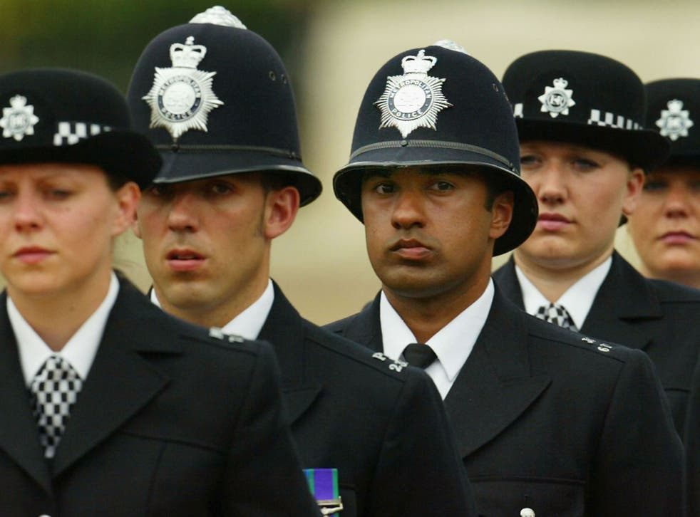 A black British police officer stands to attention during the Metropoitan Police Service's 175th Anniversary service on June 4, 2004 in London, England. The service was attended by various sections of the modern day police family.