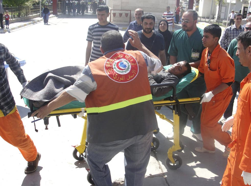 A man is brought to a hospital on a stretcher after after being wounded in a clash between Iraqi forces and Sunni Muslim protesters in Kirku