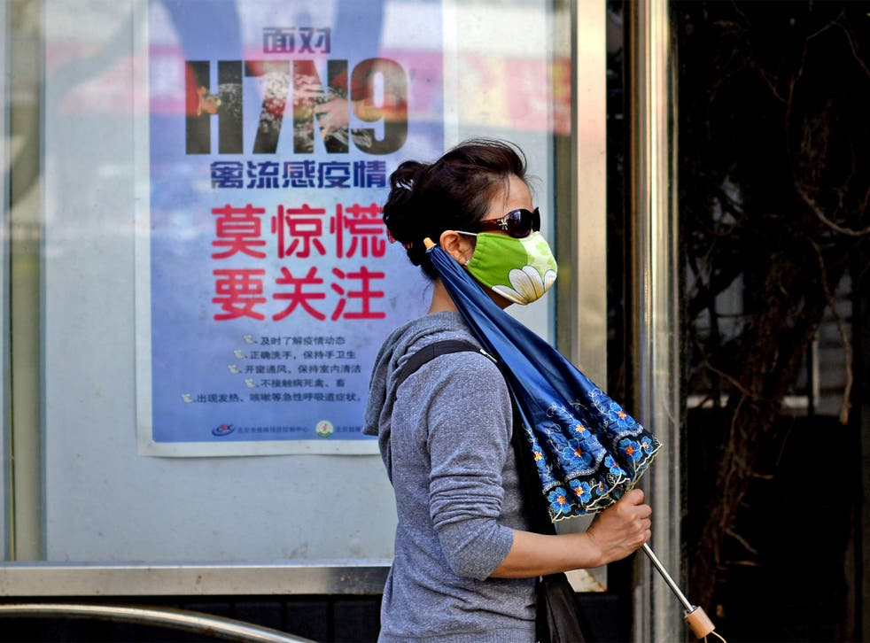 A woman wears a face mask as she walks past a poster in Beijing showing how to avoid getting the H7N9 bird flu virus