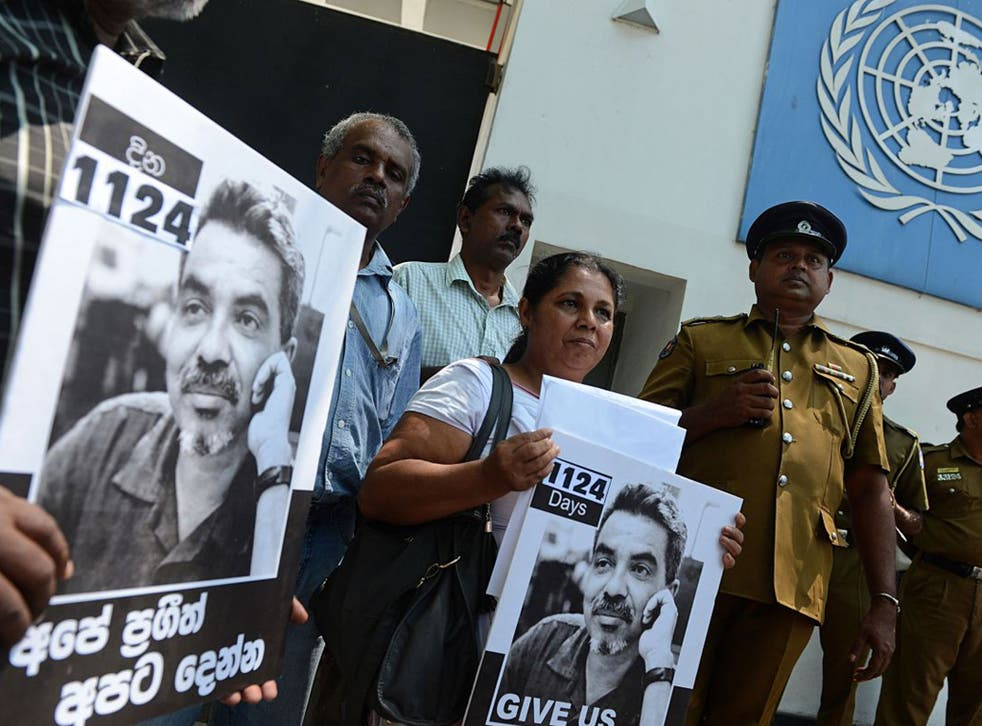 Sandhya Eknaligoda (C), wife of missing Sri Lankan cartoonist Prageeth Eknelygoda, holds a placard bearing his image outside the United Nations offices in Colombo on February 21, 2013. Eknaligoda urged UN intervention to locate her husband, missing since