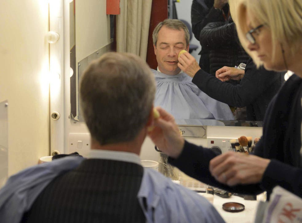 """UK Independence Party (UKIP) leader Nigel Farage sits wearing make-up before appearing in the """"BBC Vote 2013"""" studio at Milbank in London"""