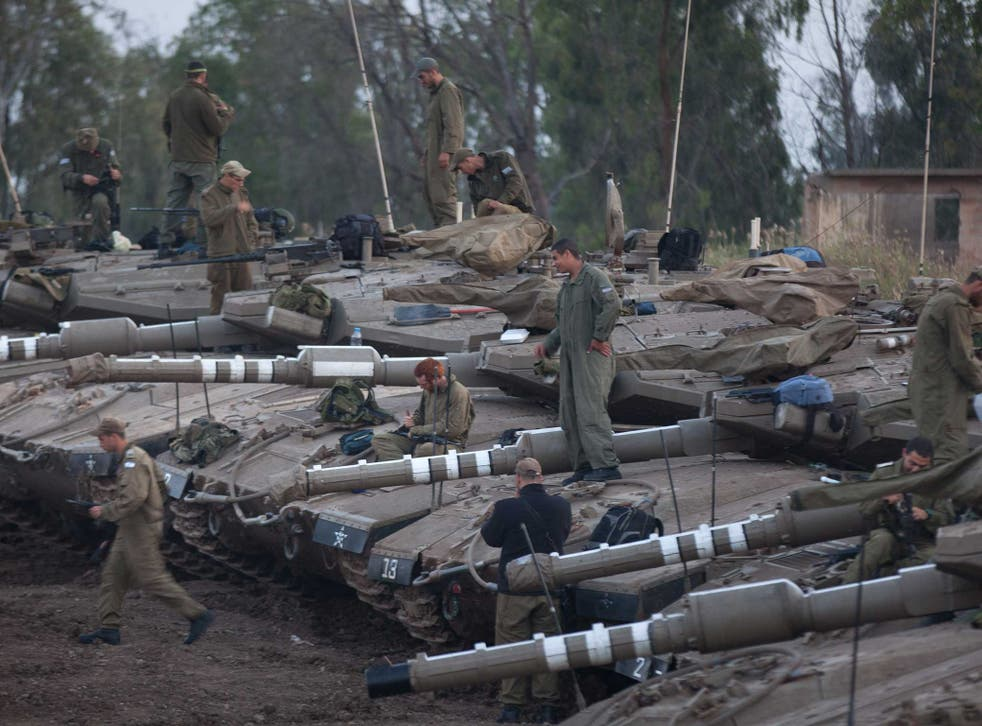 Israeli soldiers maintain their Merkava tanks at a deployment area near the border with Syria