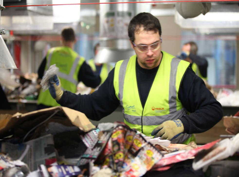 A worker sorts through the recycling at the £60m Veolia plant in Southwark, London