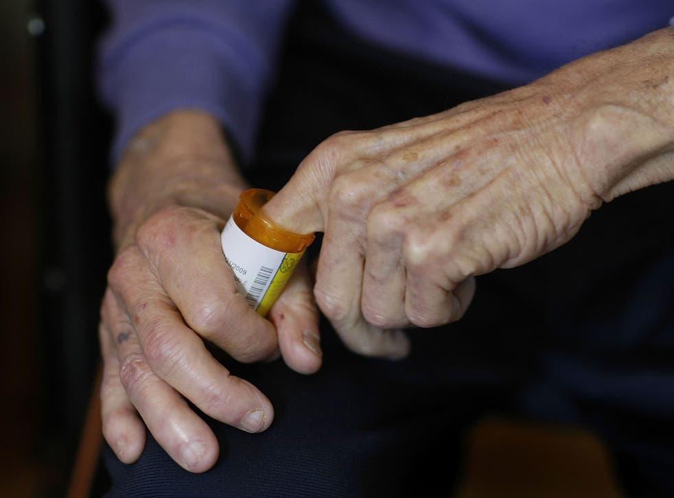 A man reaches into a medicine bottle as he takes prescription pills.