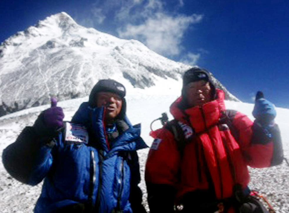 Eighty-year-old Japanese adventurer Yuichiro Miura (R) and his son Gota (L) posing for a picture as they leave the C4 camp to ascent to the summit of Mount Everest in Nepal
