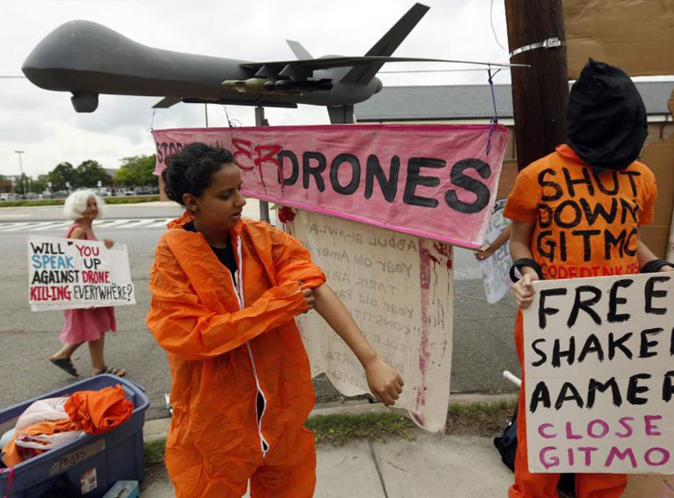 A demonstrator puts on a prison-style jumpsuit as she joins a protest beside a mock drone at the gates of Fort McNair where President Barack Obama will speak at the National Defense University in Washington