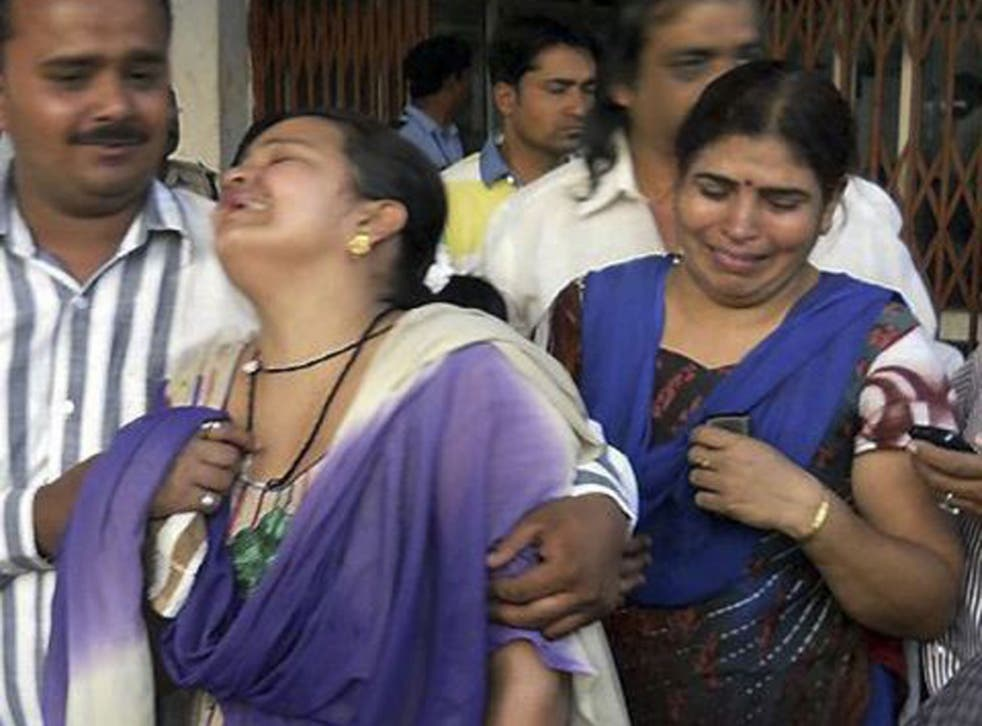 Unidentified relatives of an injured victim of a rebel attack cry outside a government hospital in Raipur, India