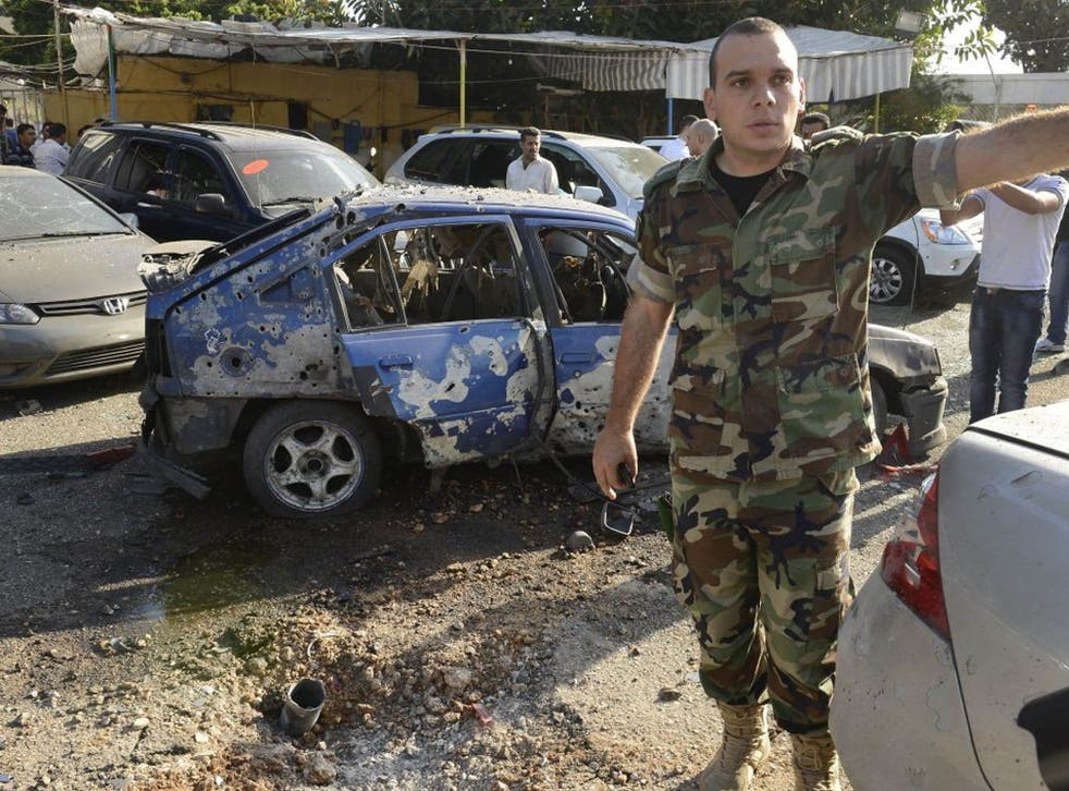 A Lebanese army officer stands next to a damaged car as he asks journalists to step back, at the scene where a rocket struck a car exhibit