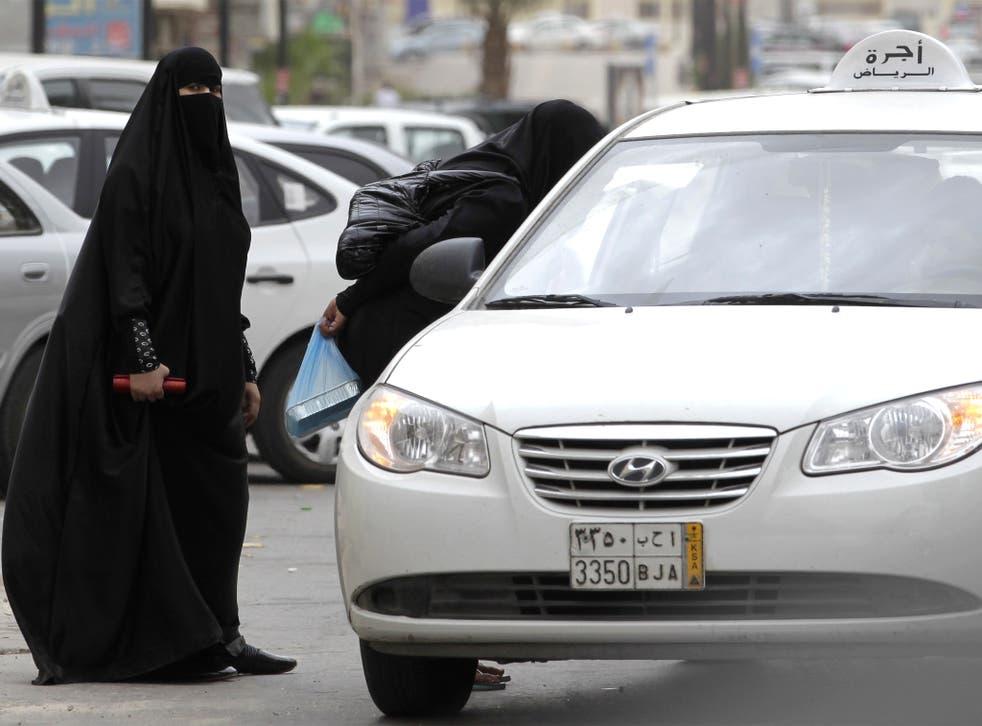 Saudi women, forbidden to drive, board a taxi in Riyadh