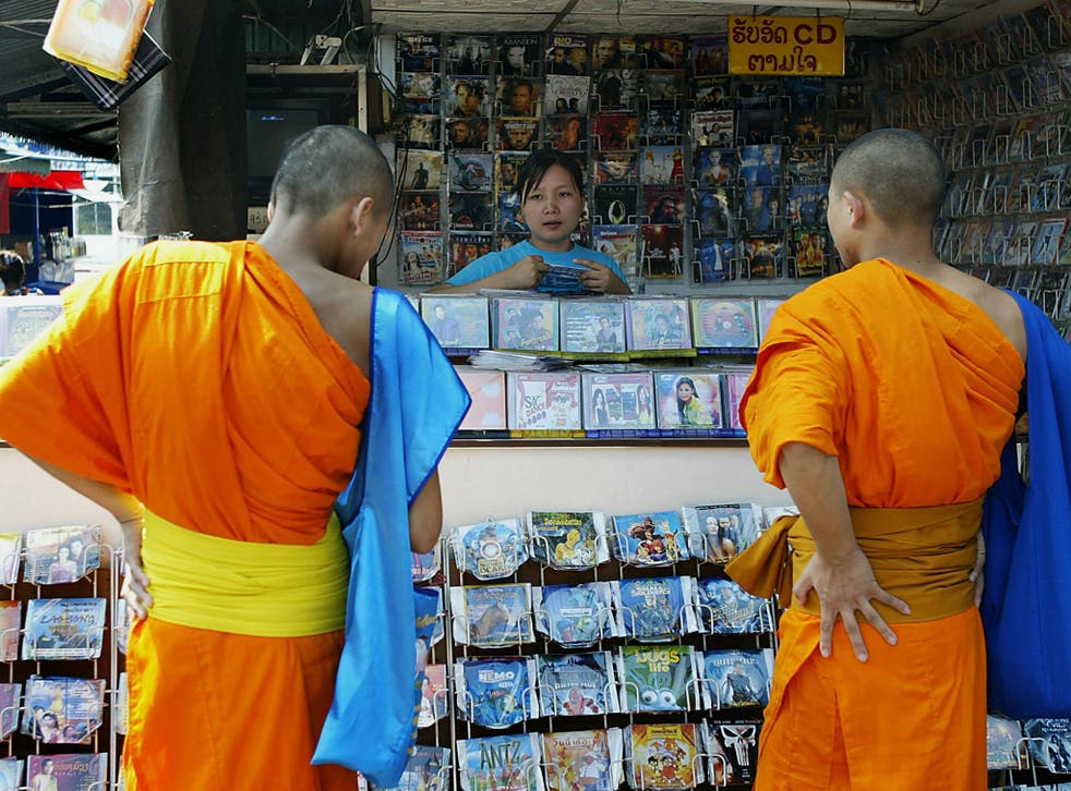 Two monks check out a CD shop selling pirated movies and music albums in Vientiane, the Laotian capital, 02 December 2004.