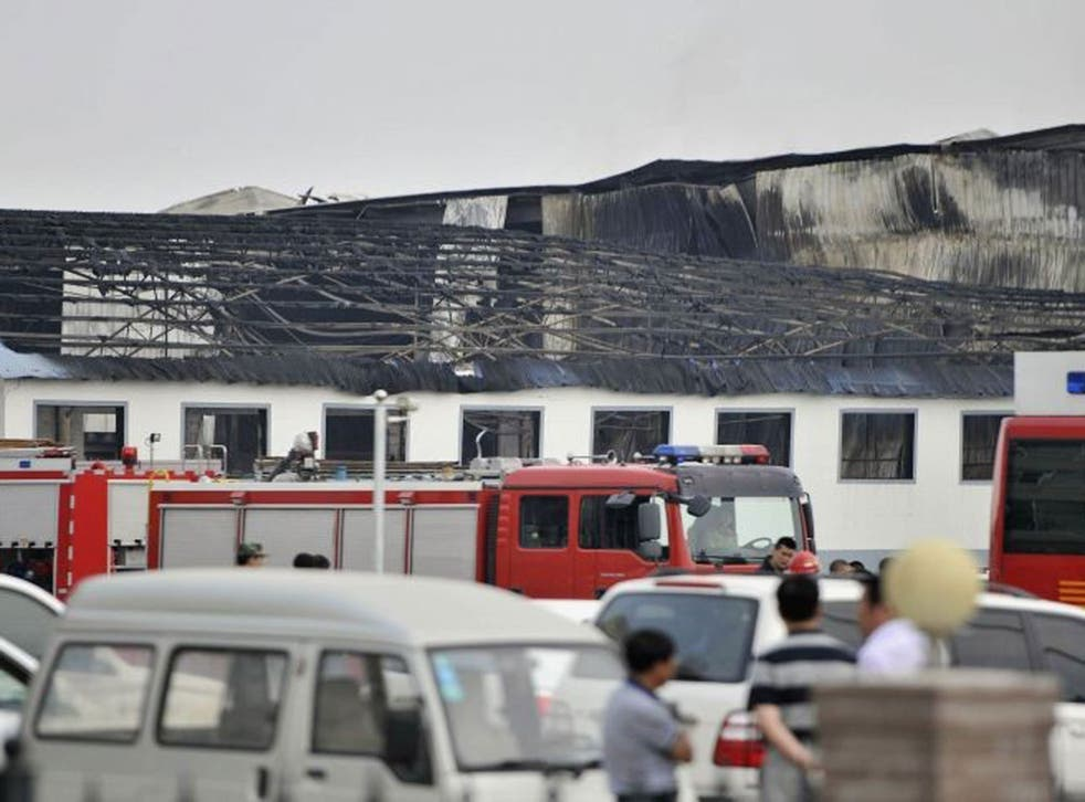 Rescue workers and fire trucks are seen outside a site of a fire, at a poultry slaughterhouse in Dehui, Jilin