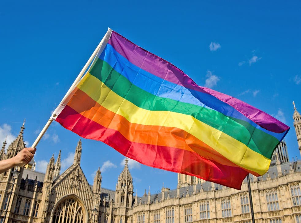 A supporter of same-sex marriage waves a rainbow flag outside the Houses of Parliament