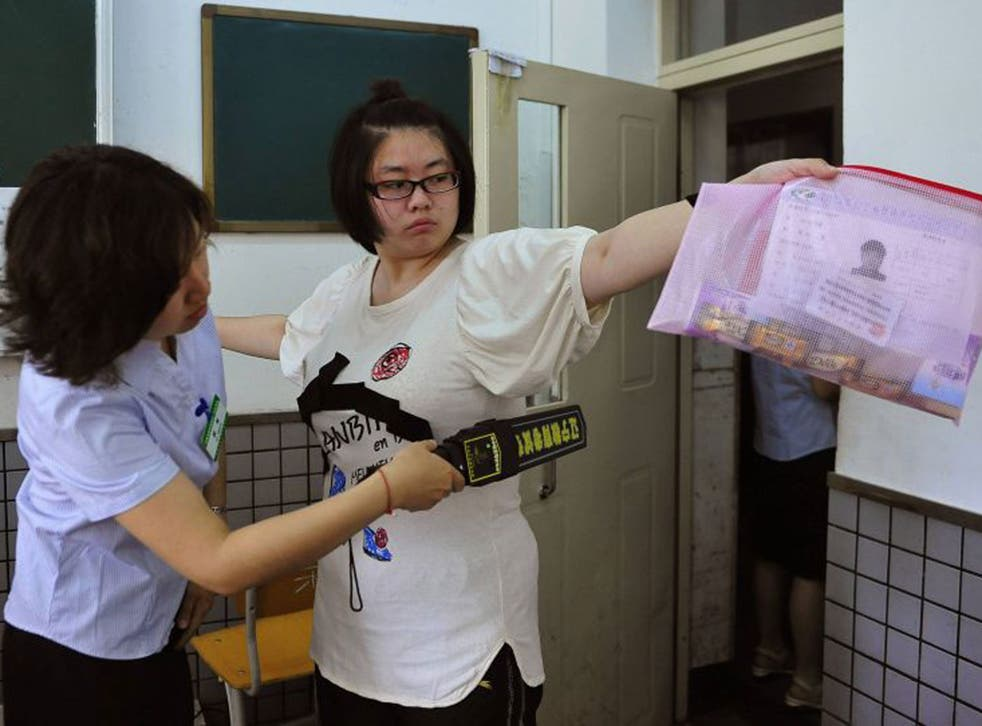 A student goes through a security check as she enters an exam room in Shenyang