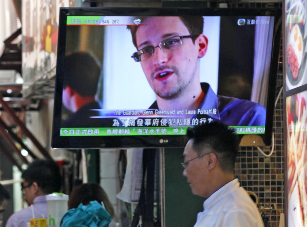 A TV screen shows Edward Snowden appearing on the news, at a restaurant in Hong Kong
