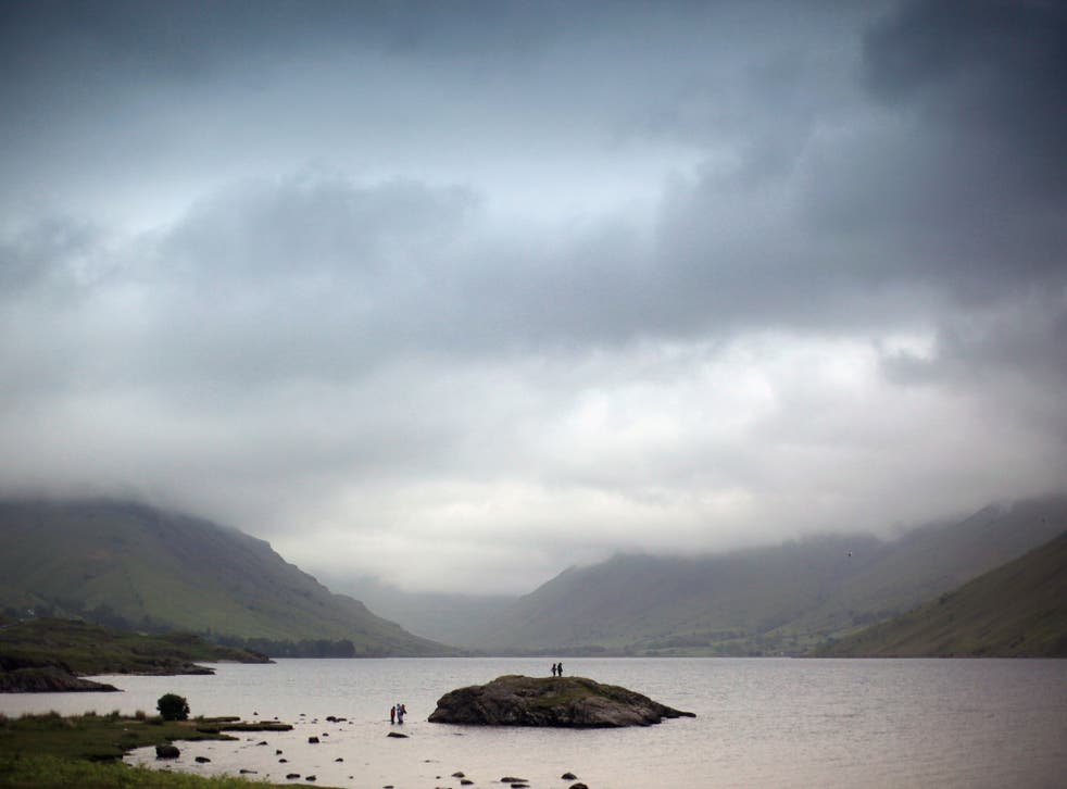 Children paddle against the backdrop of Wastwater in the Lake District