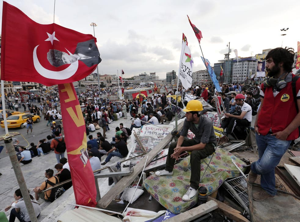 Anti-goverment protesters unfurl the Turkish national flag in Taksim