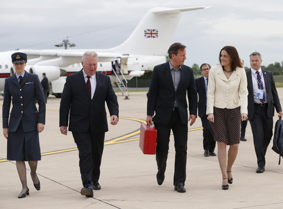 Britain's Prime Minister David Cameron walks with Northern Ireland Secretary Theresa Villiers (second right) and Wing Commander Faye Wiseman (left) after arriving in Belfast, Northern Ireland