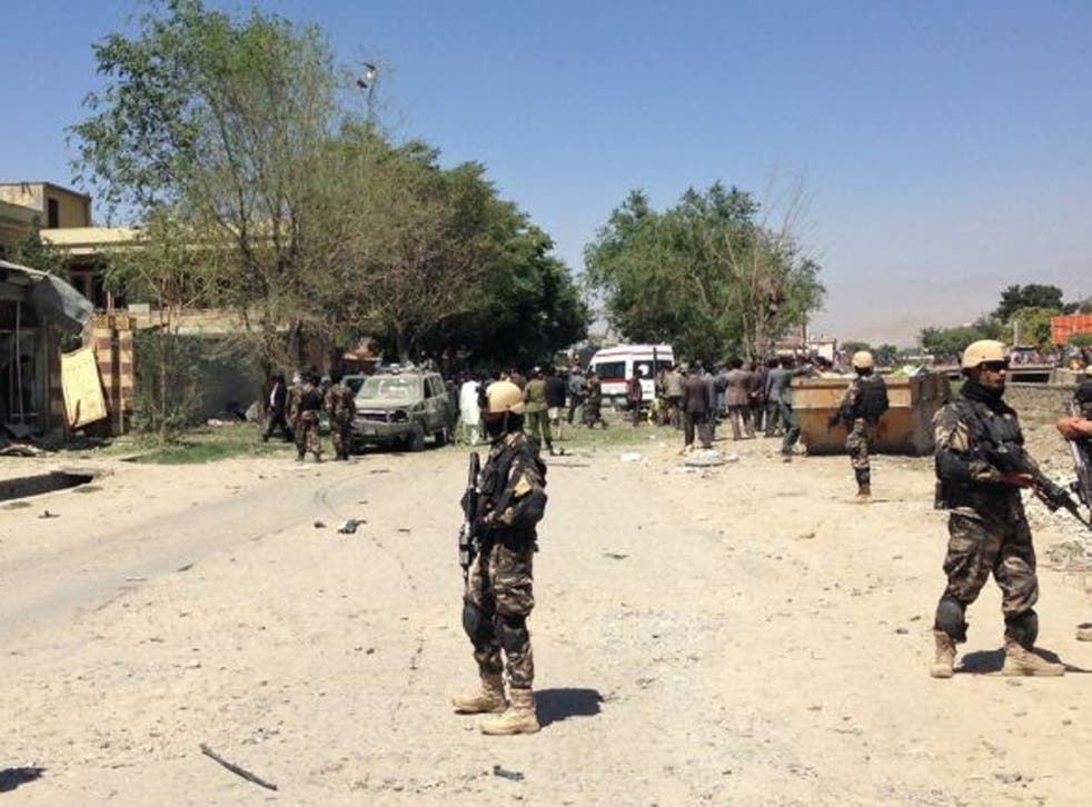 Afghanistan security forces stand guard at the site of a blast