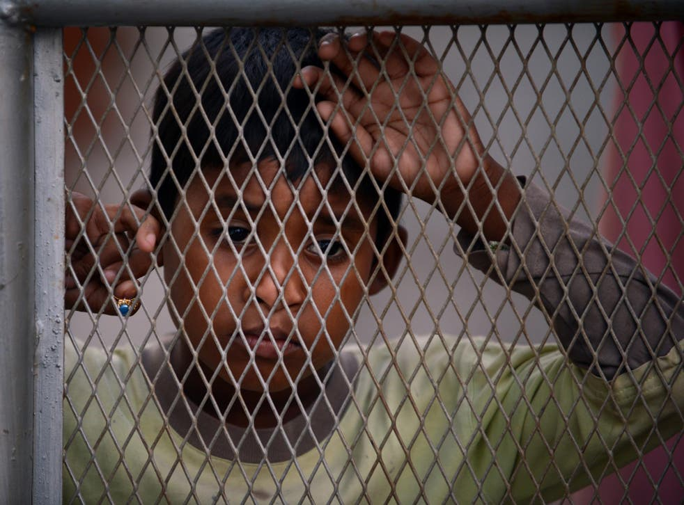 A young Myanmar Muslim Rohingya refugee looks on behind a wired fence