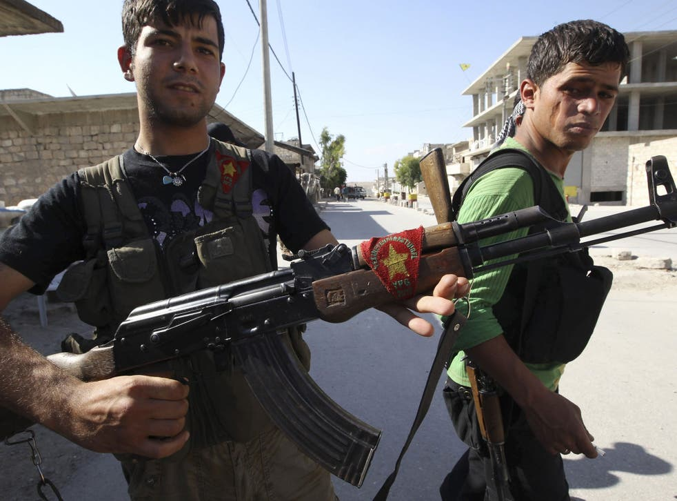 A Kurdish fighter from the Popular Protection Units (YPG) shows his weapon decorated