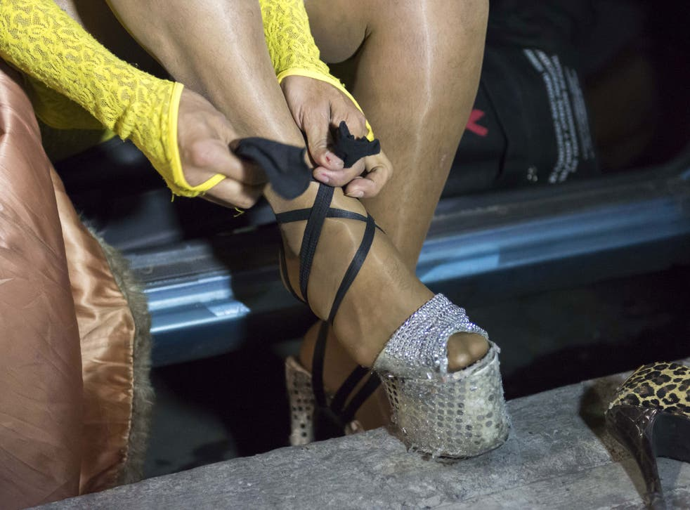 HIV-positive transsexual sex worker Tesoro (Treasure in Spanish) adjusts her shoe at the corner where she works in Mexico City on June 18, 2013.