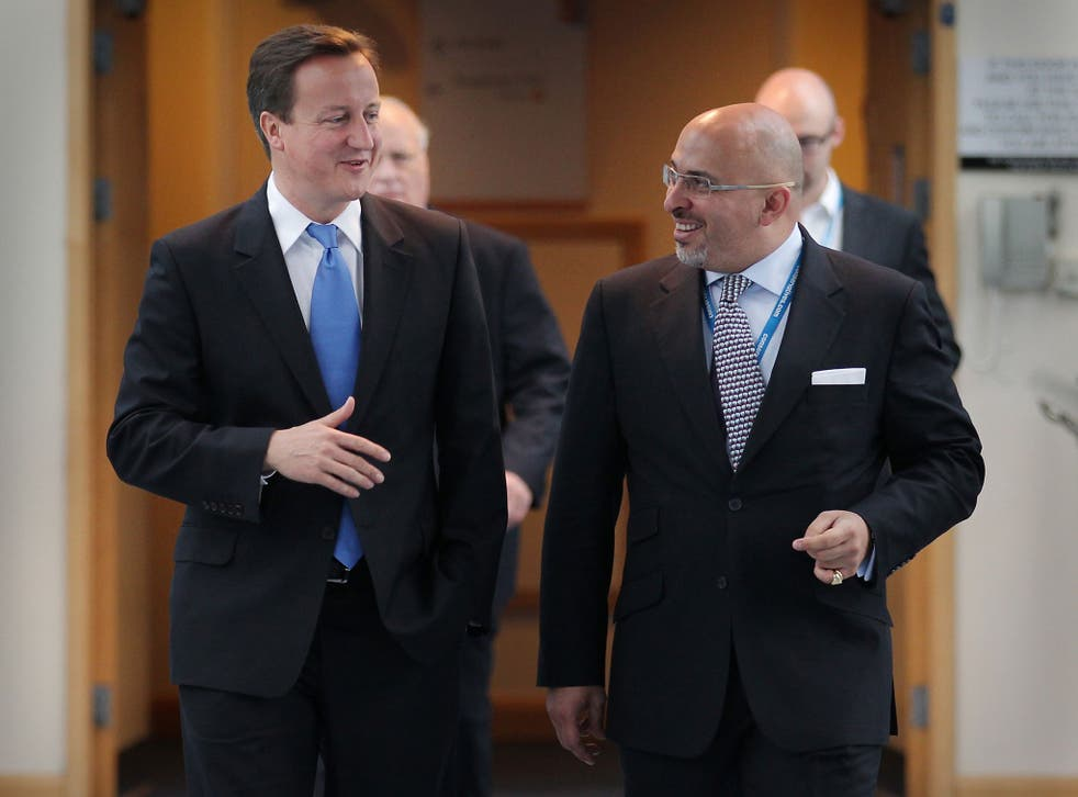Prime Minister David Cameron (L) walks with Conservative MP Nadhim Zahawi at the Conservative Party Conference during a television interview on October 5, 2010 in Birmingham, England