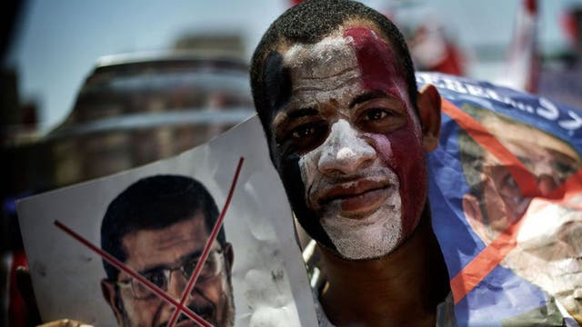 An Egyptian holds up posters during a protests against President Mohamed Morsi and the Muslim Brotherhood as they join thousands at Egypt's landmark Tahrir square