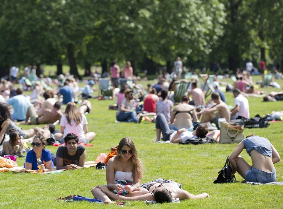 People sunbathe in the summer heat in a park in central London