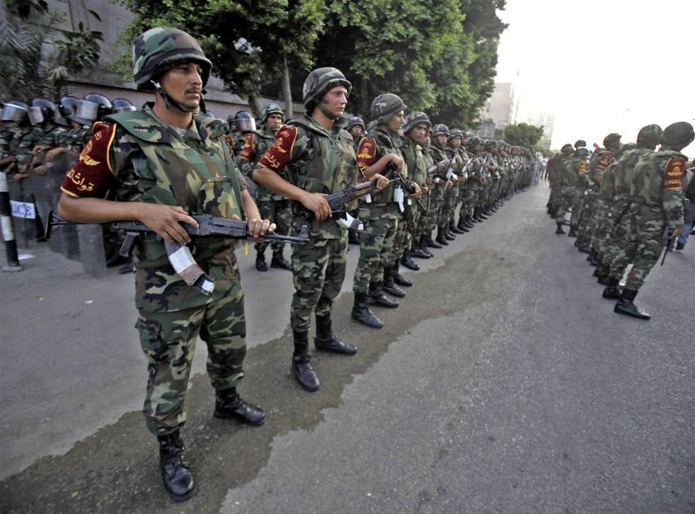 Army soldiers take their positions in front of protesters