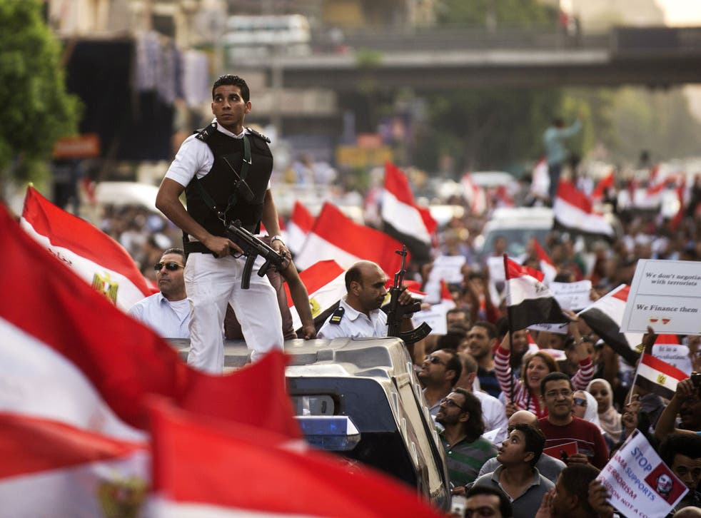 Policemen amid protesters demonstrating against the deposed President Mohammed Morsi
