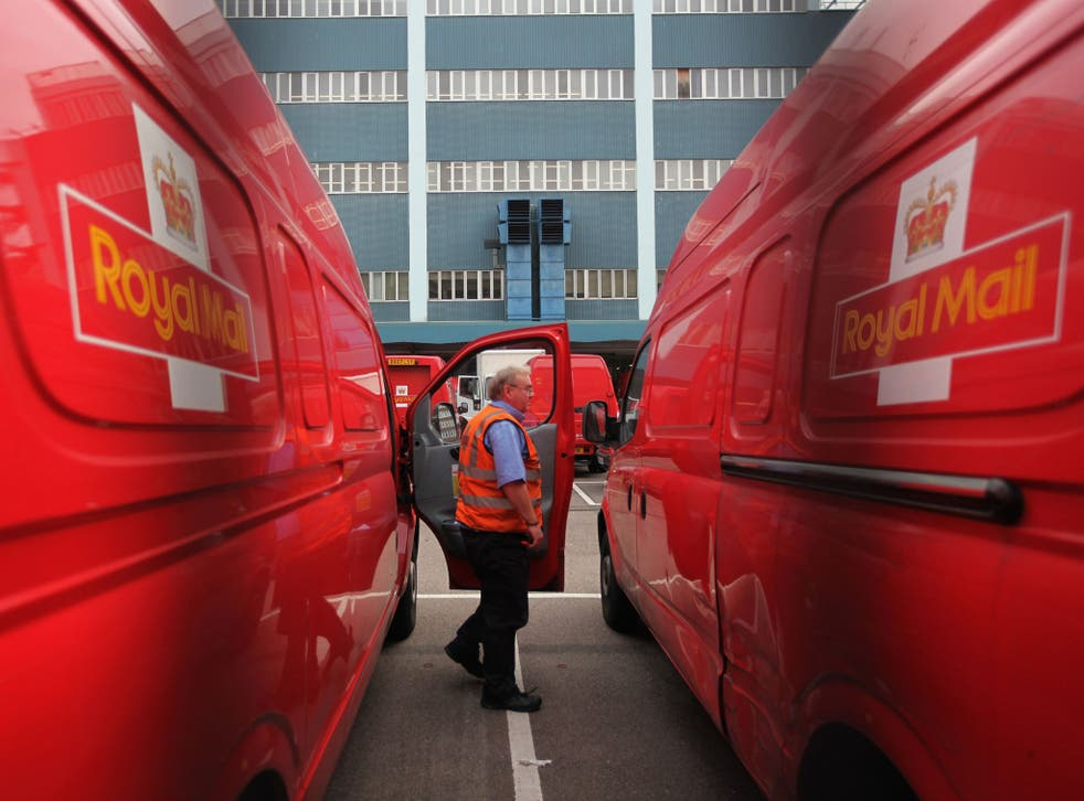 A Royal Mail employee steps out of a delivery van at the Rathbone Place Royal Mail depot in London