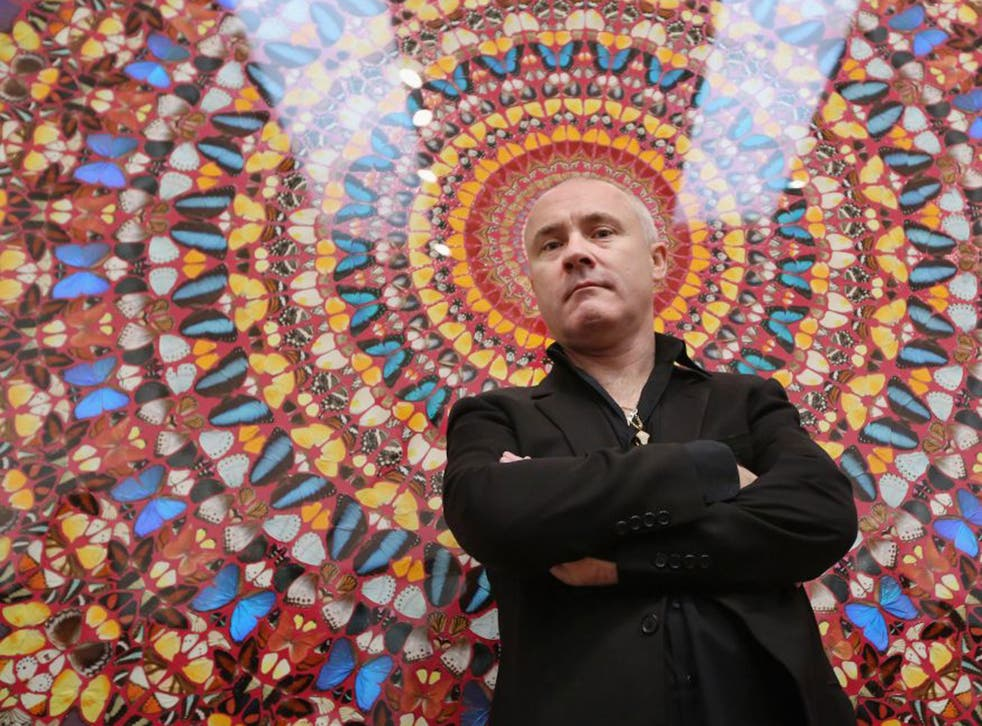 Artist Damien Hirst poses in front of his artwork entitled 'I am Become Death, Shatterer of Worlds' in the Tate Modern art gallery