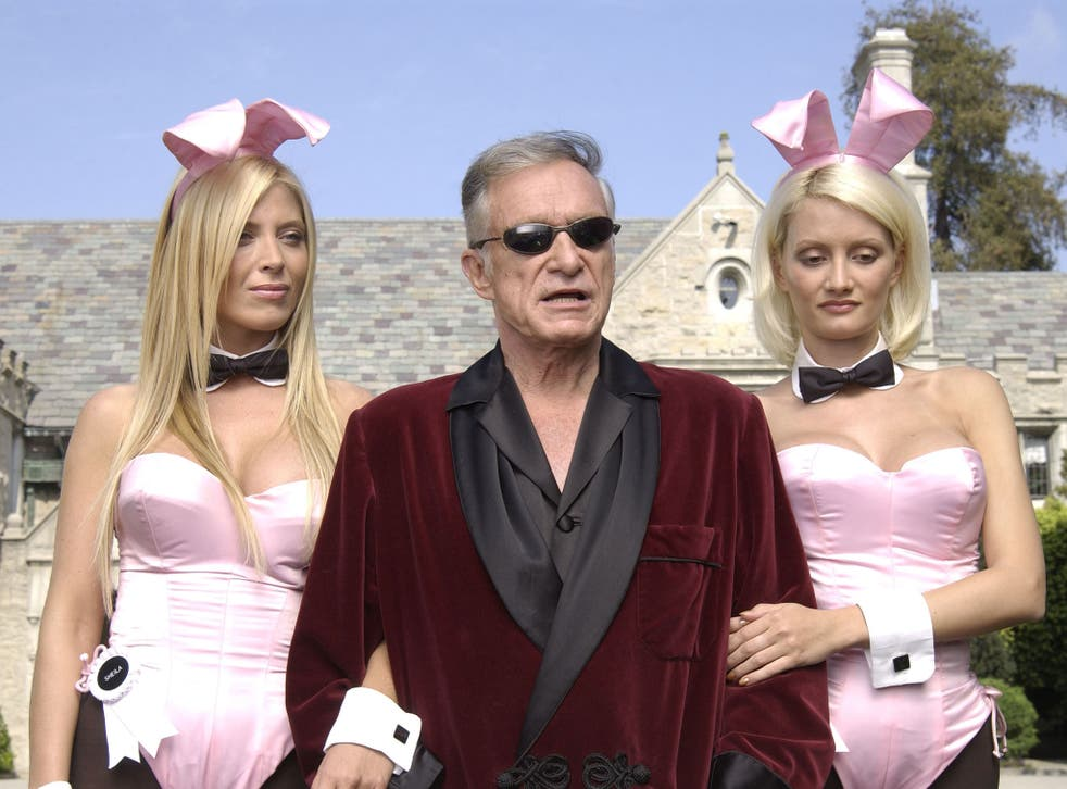 Playboy bunny Sheila Levell, Playboy founder Hugh Hefner and Playboy bunny Holly Madison perform a scene during the filming of a commercial for 'X Games IX' at the Playboy Mansion May 6, 2003 in Holmby Hills, California.