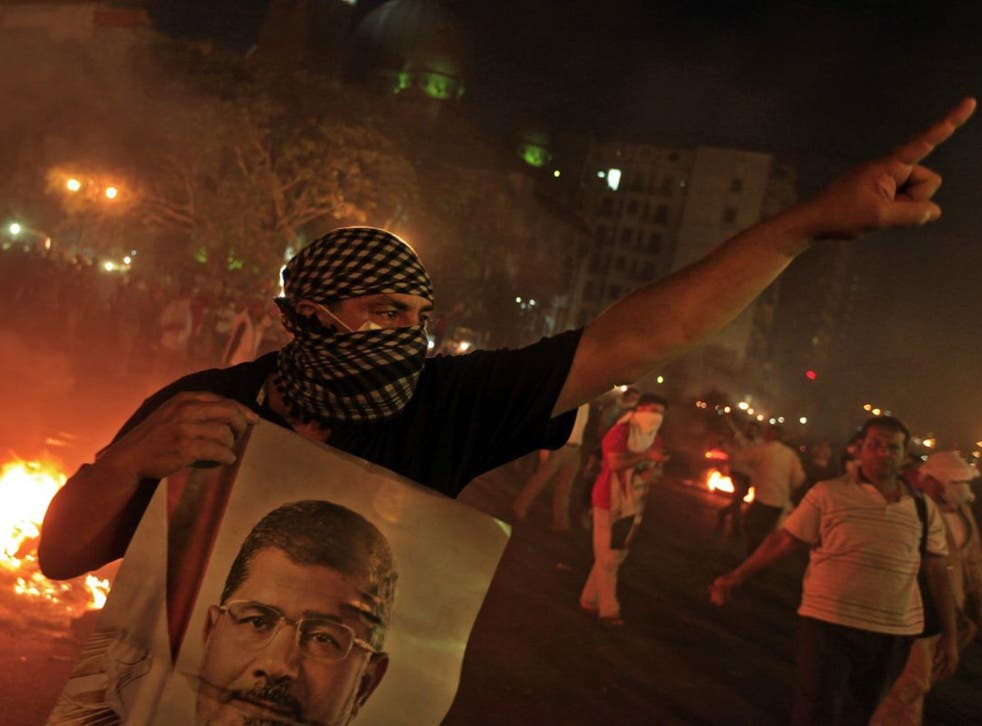 A Morsi support holds a poster of him during the clashes in Cairo last night