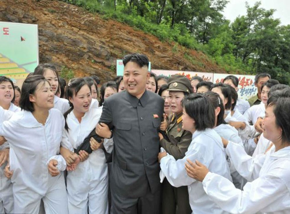 A smiling Kim Jong-un is seen being mobbed by a large group of crying women wearing white boiler suits