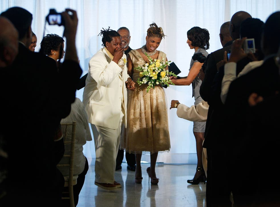 Angelisa Young (R) and Sinjoyla Townsend (L) rejoice as Rev. David North (C) looks on during their wedding on the first day same-sex couples are legal to wed under a new law March 9, 2010 in Washington, DC.