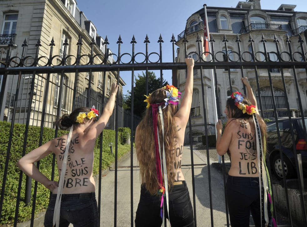 22 July 2013: Members of Femen Belgium shout slogans outside the gates of the Tunisian embassy after they used a chain to lock the gates, during a protect calling for the release of fellow activist Tunisian Amina Tyler, in Brussels
