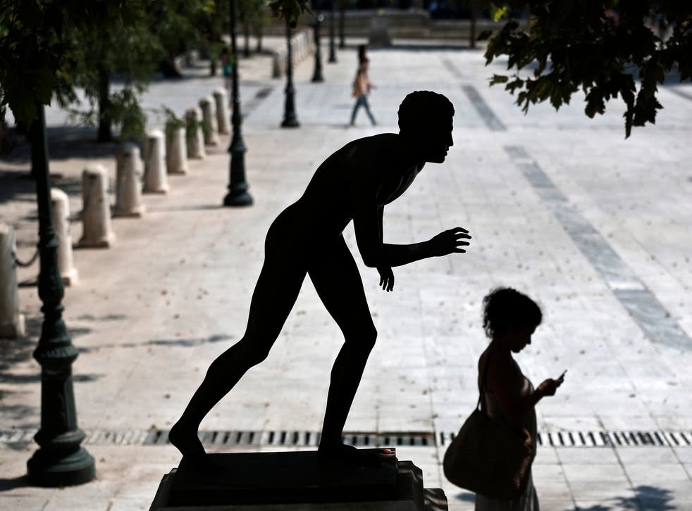 A woman checks her mobile phone as she walks past a statue at central Syntagma square in Athens July 3, 2013. REUTERS/Yorgos Karahalis