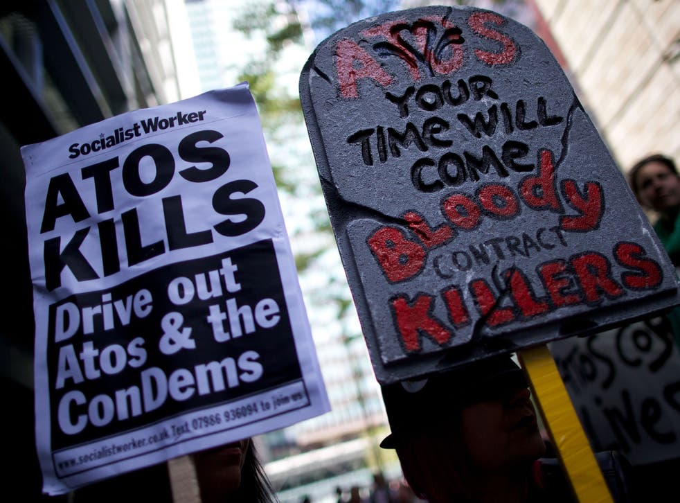 Protesters carry placards during a protest against Atos outside the company's head office in London last year