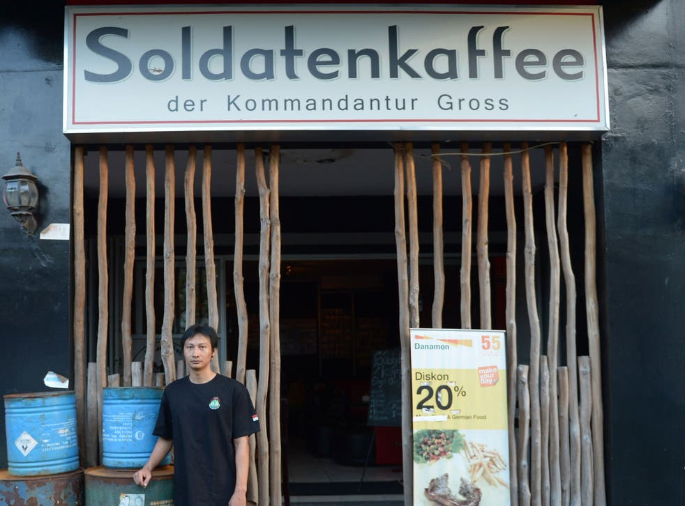 Henry Mulyana standing outside the Soldatenkaffe 'The Soldiers' Cafe' in Bandung