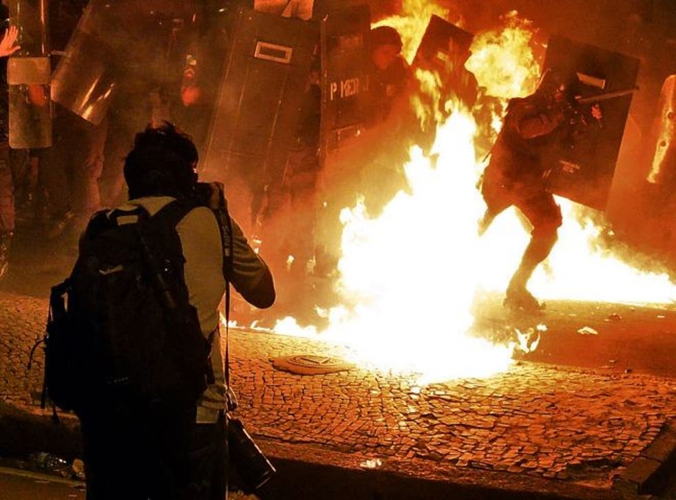 A photographer captures clashes between protesters and riot police in Rio de Janeiro