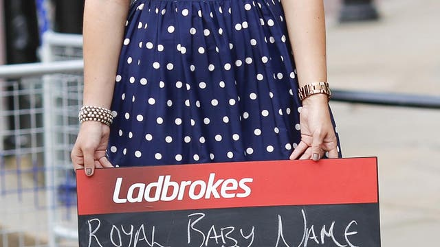 A woman holds a Ladbrokes board listing possible baby names to bet on as media gather outside Buckingham Palace to read the easel displaying the announcement of the son of The Duke and Duchess of Cambridge