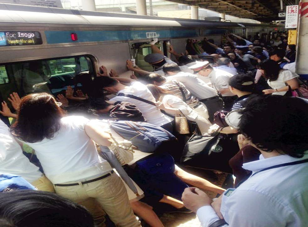 Train passengers and railway staff push a train car in their effort to rescue a woman who fell and got stuck between the car and the platform while getting off at Japan Railway Minami Urawa Station in Saitama, near Tokyo