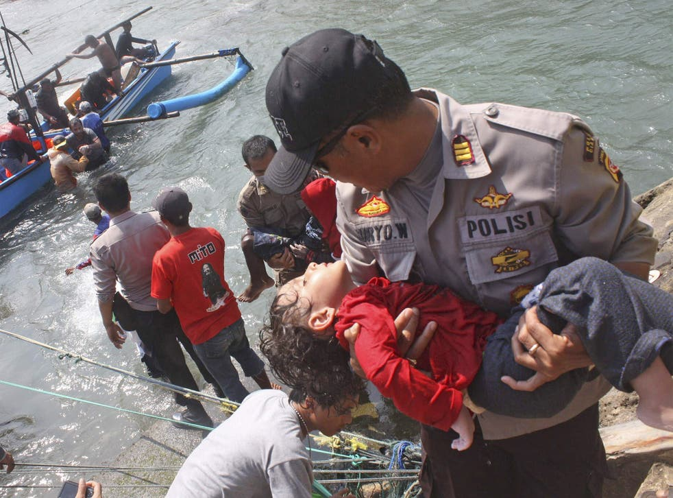 A police officer carries a child survivor who was on the boat full of asylum seekers that capsized off the coast of Sukapura, Indonesia. Nine people died but 189 refugees were rescued