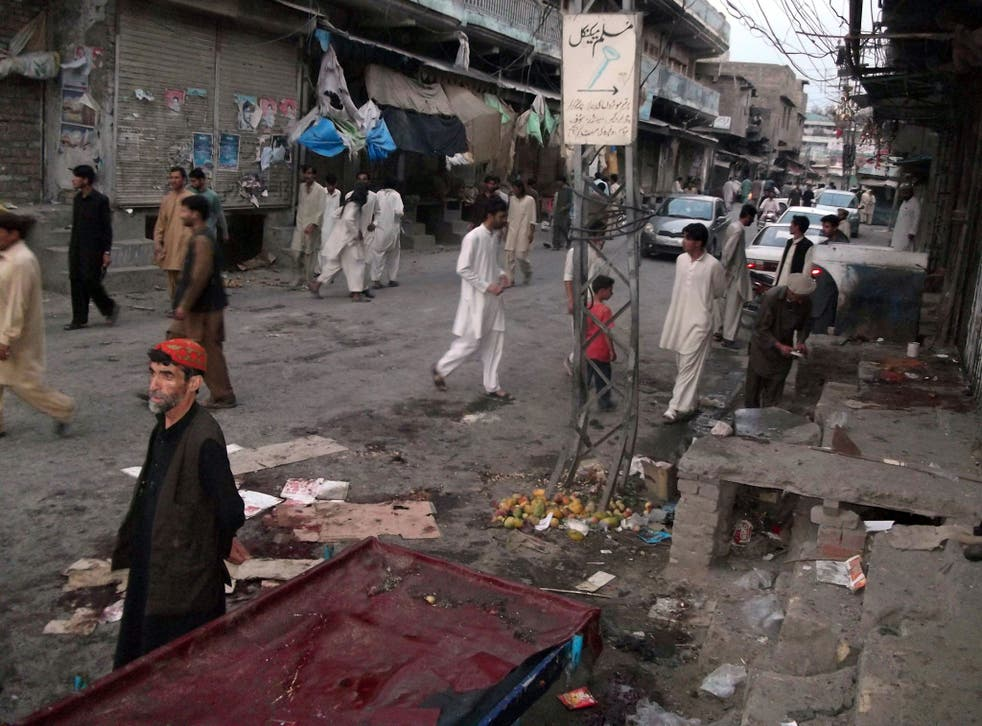 Pakistani residents gather at the site of twin bomb explosions in Parachinar, the main town of Kurram tribal district
