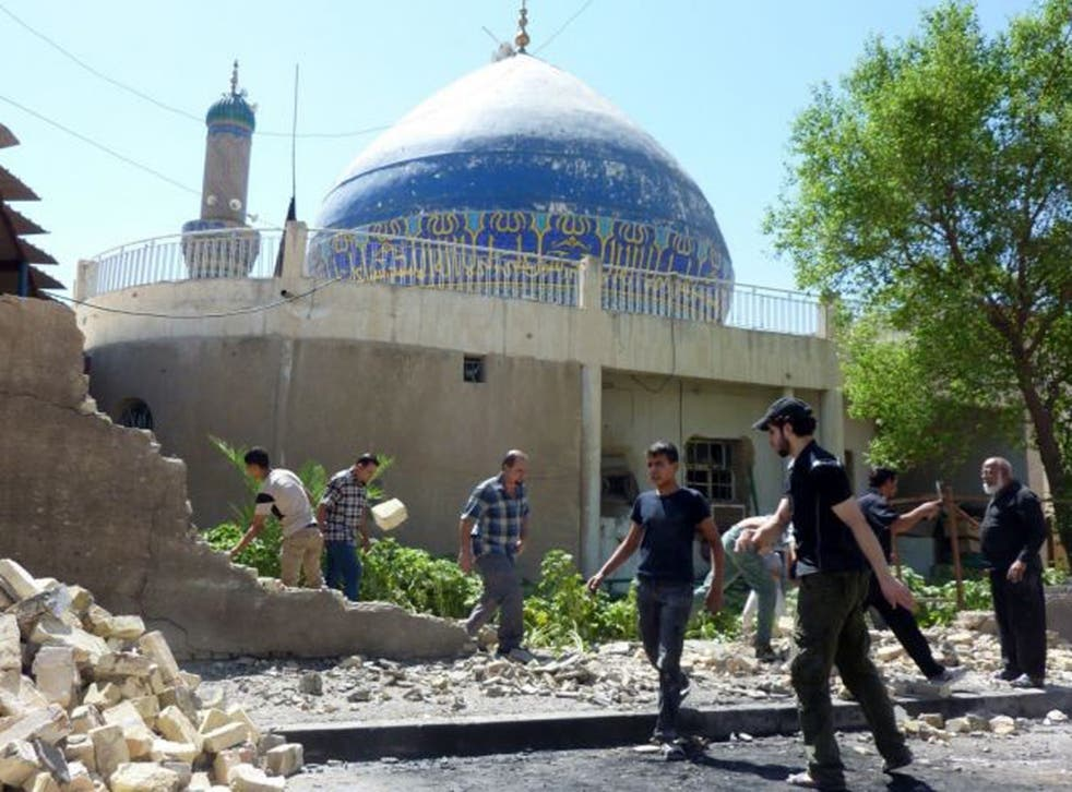 Iraqis remove the stones of a wall destroyed in a car bombing outside Ahl al-Bayya' mosque on 29 July 2013 in south-eastern Baghdad