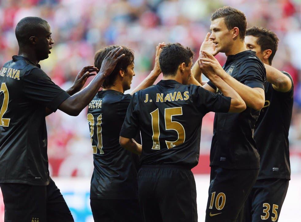 Edin Dzeko is congratulated by team-mates after scoring against AC Milan