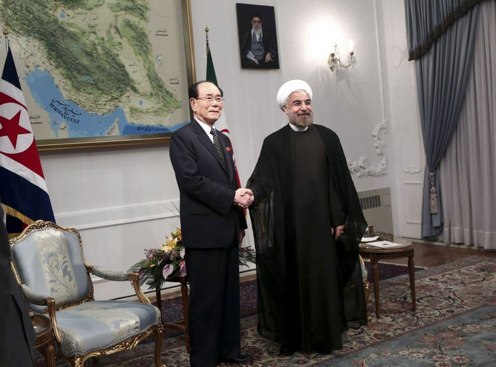 Iranian President Hasan Rouhani, right, shakes hands with a top North Korean leader, Kim Yong Nam, at the start of a meeting in Tehran