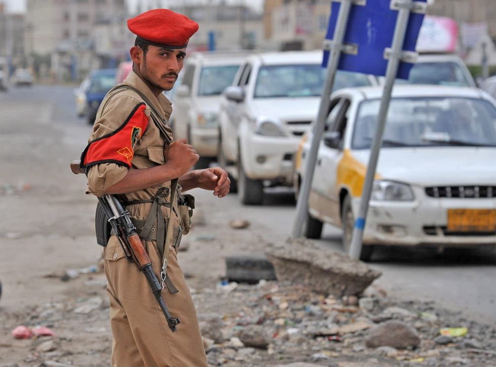 A Yemeni soldier stands guard at a checkpoint on a street leading to the US embassy
