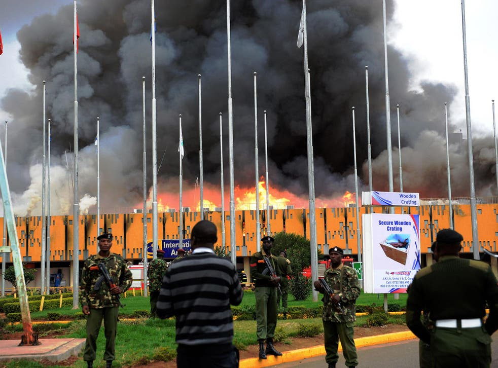 General Service (GSU) officer stand outside the burning Jomo Kenyatta international airport. A massive fire shut down Nairobi's international airport today with flights diverted to regional cities as firefighters battled to put out the blaze in east Afric